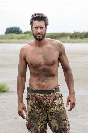 hombres sin camisa: Close up retrato de Confiado magnífico Atlético Ejército sin la camisa posando en la playa sin camisa. Foto de archivo