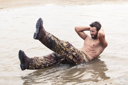 military training: Handsome Muscled Soldier with no Shirt Doing Curl Ups Exercise at the Sea Water Stock Photo