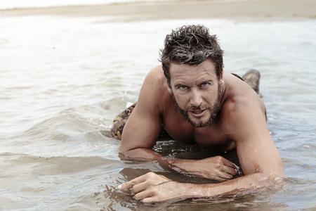 tenacious: Close up Handsome Athletic Army with No Shirt Crawling at Sea Water While Looking at the Camera.