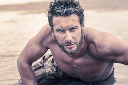 hombres sin camisa: Cierre de guapo Atl�tico Ej�rcito sin la camisa que se arrastra en el mar de agua mientras mira a la c�mara. Foto de archivo