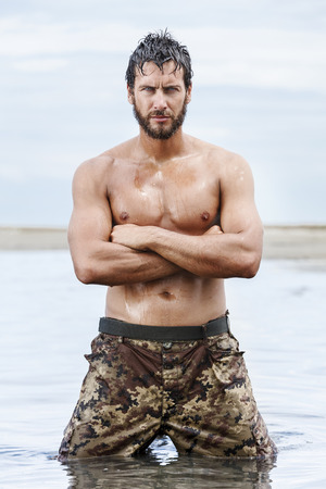 hombre fuerte: Close up retrato de Confiado magn�fico Atl�tico Ej�rcito sin la camisa posando en el mar sin camisa.