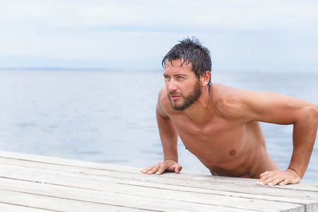 inscrutable: Close up Portrait of Sexy Confident Handsome Man with No Shirt at the Sea Stock Photo