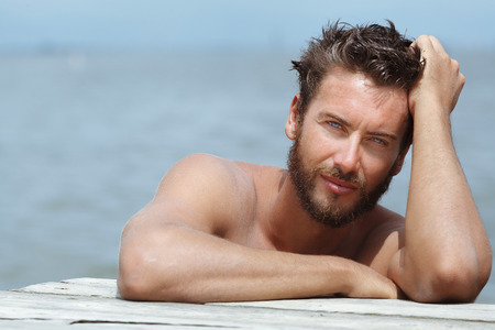 charming: Close up Portrait of Smiling Gorgeous Handsome Man with No Shirt Posing at the Sea