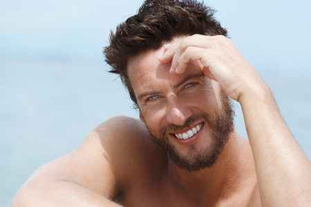 Close up Portrait of Smiling Handsome Man with No Shirt Smiling at the Sea photo