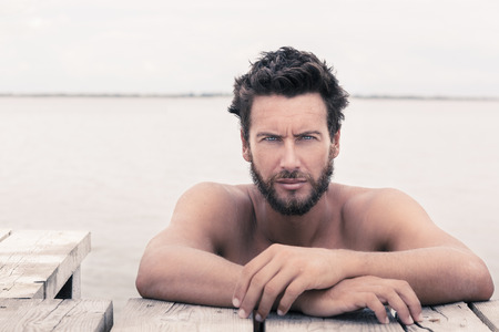 beau mec: Close up portrait d'Confiant magnifique Handsome Man sans chemise Posing à la mer Banque d'images