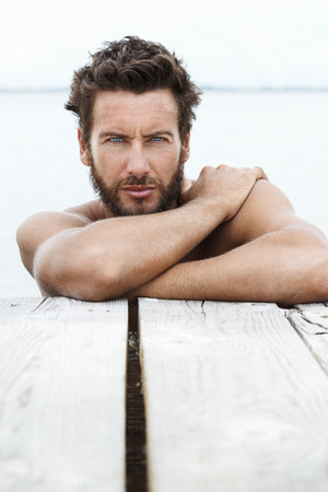Close up Portrait of Sexy Handsome Man with beard and No Shirt Posing at the Sea