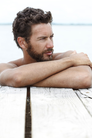 Close up Portrait of Handsome Man with beard and No Shirt Posing at the Sea photo