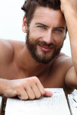 Close up Portrait of Smiling Handsome Man with No Shirt Posing at the Sea photo