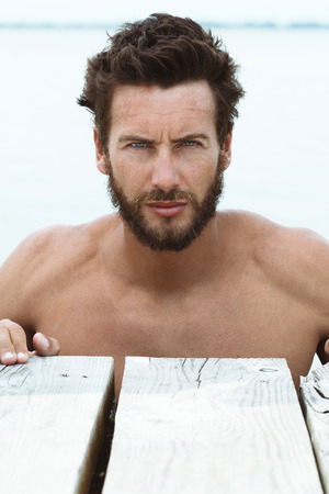 Close up Portrait of Confident Athletic Handsome Man with No Shirt Posing at the Sea photo