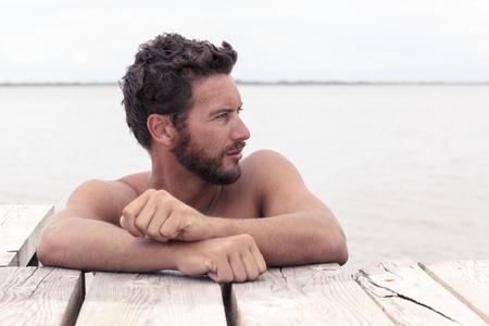 Zblízka Portrét sebevědomý Pohledný muž s bez košile představuje v moři