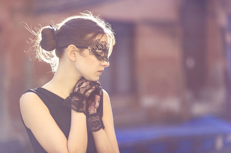 lace gloves: Stylish Young Woman Wearing Elegant Black Masquerade Mask and Lace Gloves with Both hands Below the Chin.