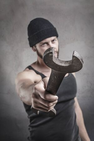 brandishing: Aggressive man using a wrench as a weapon raising it threateningly in front of him with an arm extended focus to the end of the spanner Stock Photo