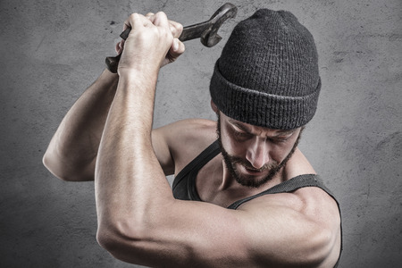 vengeful: Violent man using a spanner or wrench as a weapon beating down with blows on something below him close up head and shoulders Stock Photo