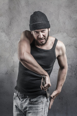 thug: Thug preparing to use a wrench as a weapon pulling it out of the pocket of His jeans as he watches the camera with a dangerous angry expression over a textured gray background
