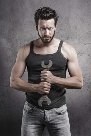 Handsome rough casual man standing holding a wrench over a textured grey background