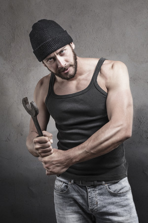 vindictive: Thug preparing to use a wrench as a weapon with a dangerous angry expression over a textured gray background looking at camera