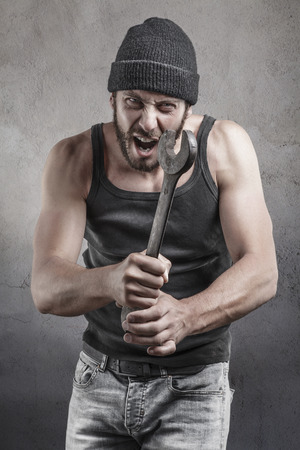 thug: Angry hooligan or thug shouting a threatening with a raised wrench during a violent crime or mugging over a grey background Stock Photo