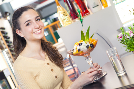 ice cream glass: Portrait of young and smiling beautiful woman eating a fruit and ice cream dessert in a bar Stock Photo