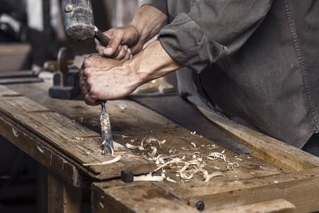 menuisier: Carpenter avec un marteau et un burin sur le plan de travail en bois dans la menuiserie