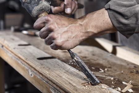 carpintero: Manos del carpintero con cincel en las manos sobre la mesa de trabajo en la carpintería
