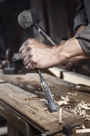 carpentry: hands of carpenter with a hammer and chisel on the workbench in carpentry