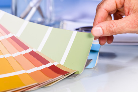 sampler: Close up of Artist hand browsing color samples in palette in studio background Stock Photo