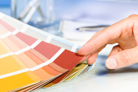 designer at work: Close up of Artist hand browsing color samples in palette in studio background Stock Photo