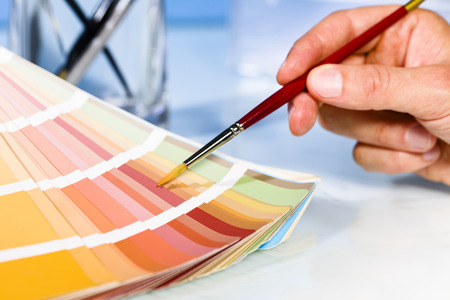 graphic artist: Close up of Artist hand pointing to color samples in palette with paintbrush in studio background Stock Photo