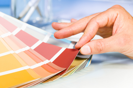 choosing: Close up of Artist hand browsing color samples in palette in studio background Stock Photo