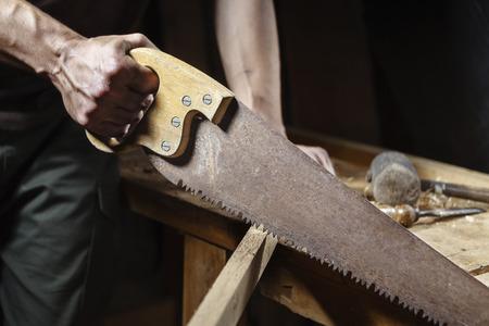 carpintero: cerca de Carpenter serrar un tablero con una sierra de madera de la mano