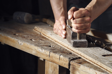 Close up of a carpenter planing a plank of wood with a hand plane