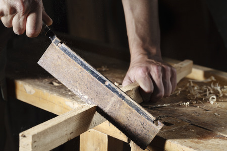 carpenter's sawdust: close up of Carpenter sawing a board with a hand wood saw Stock Photo