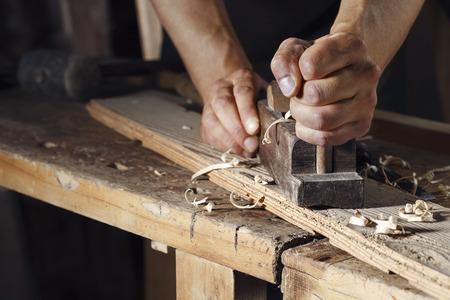 carpintero: Primer plano de un carpintero cepillar una tabla de madera con un plano de la mano