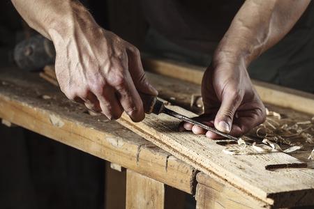 muebles de madera: Primer plano de un carpintero manos que trabajan con un cincel y herramientas de talla en el banco de trabajo de madera