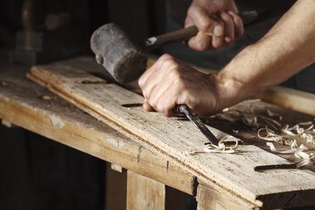 carpintero: Primer plano de un carpintero manos que trabajan con un cincel y un martillo en la mesa de trabajo de madera