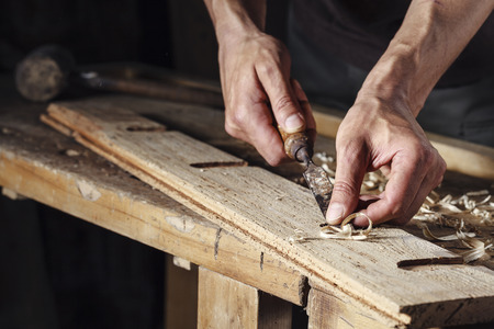 carpintero: Primer plano de un carpintero manos que trabajan con un cincel y herramientas de talla en el banco de trabajo de madera