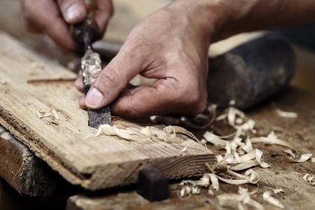 tallado en madera: Primer plano de un carpintero manos que trabajan con un cincel y herramientas de talla en el banco de trabajo de madera