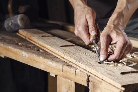 trabajando duro: Primer plano de un carpintero manos que trabajan con un cincel y herramientas de talla en el banco de trabajo de madera