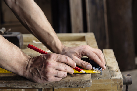 carpenter: hands of a carpenter taking measurement of a wooden plank with pencil and ruler