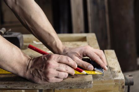 carpintero: manos de un carpintero que toma la medida de un tablón de madera con lápiz y regla
