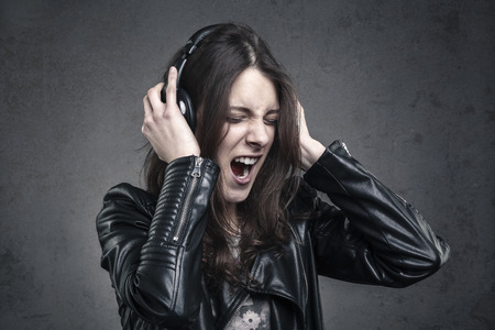 young Woman with head phones listening to music and Singing against dark wall background;