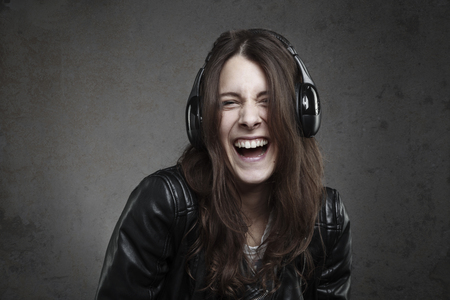 ear phones: Laughing young Woman with headphones listening music against dark wall background