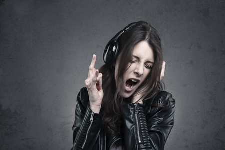 music background: young Woman with head phones listening to music and Singing against dark wall background;