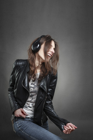 Woman dancing while listening to music with headphones against dark wall background; Stock Photo