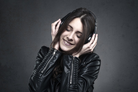 ear phones: Smiling Woman with headphones listening music against dark wall background