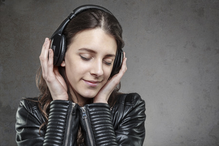 wall background: Smiling Woman with headphones listening music against dark wall background