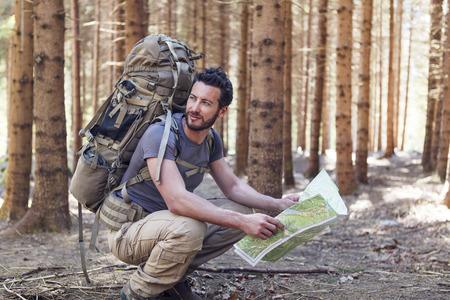 Baard Mens met rugzak en kaart te zoeken richtingen in de wildernis gebied Stockfoto