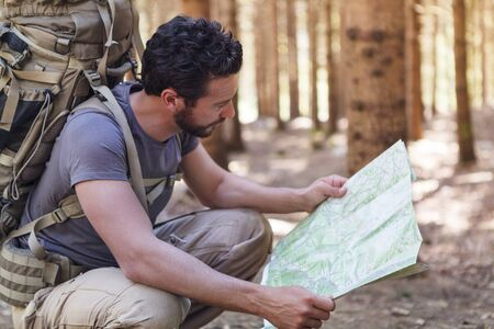lost: Beard Man with Backpack and map searching directions in wilderness area