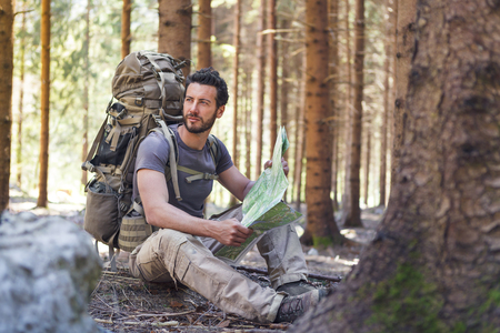 wilderness area: Beard Man with Backpack and map searching directions in wilderness area