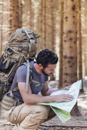 guide: Beard Man with Backpack and map searching directions in wilderness area